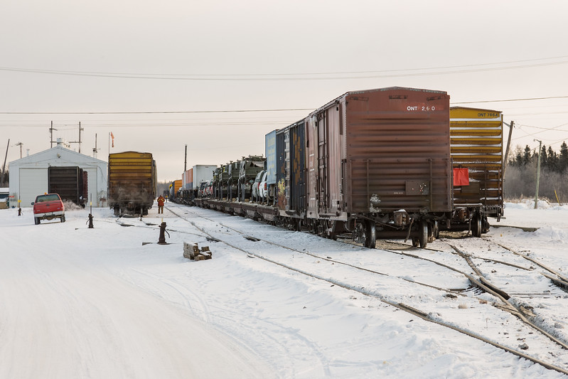"Ontario Northland mixed train ""the Little Bear"" being assembled at Moosonee, passenger consist (headed by snowmobile boxcar) is on right, one freight section including vehicles on flatcars is in centre"
