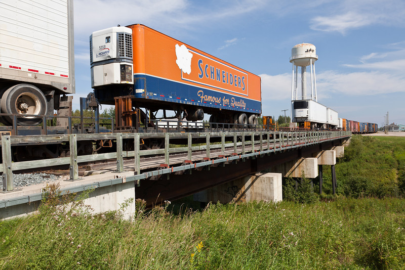 Trailers on flatcars in the consist of the twice weekly freight train cross Store Creek as they enter Moosonee, Ontario.