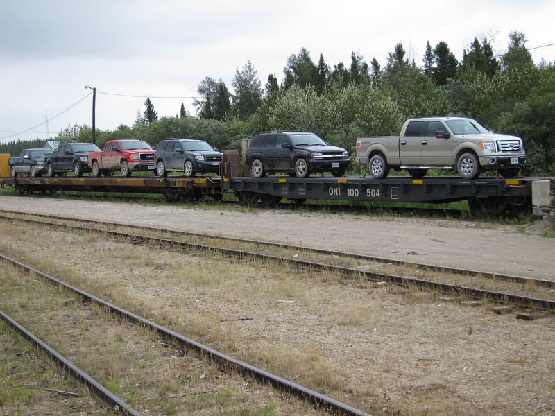 Flat cars 100505 and 100504 loaded with vehicles for travel on the Polar Bear Express train of the Ontario Northland Railway.