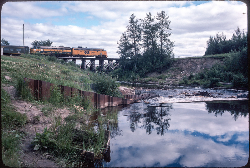 1978 August 6 Polar Bear Express crossing wooden bridge over Store Creek in Moosonee. FP7's 1510 and 1515. Store Creek dam in foreground. Slilde bought on ebay, no photographer info.