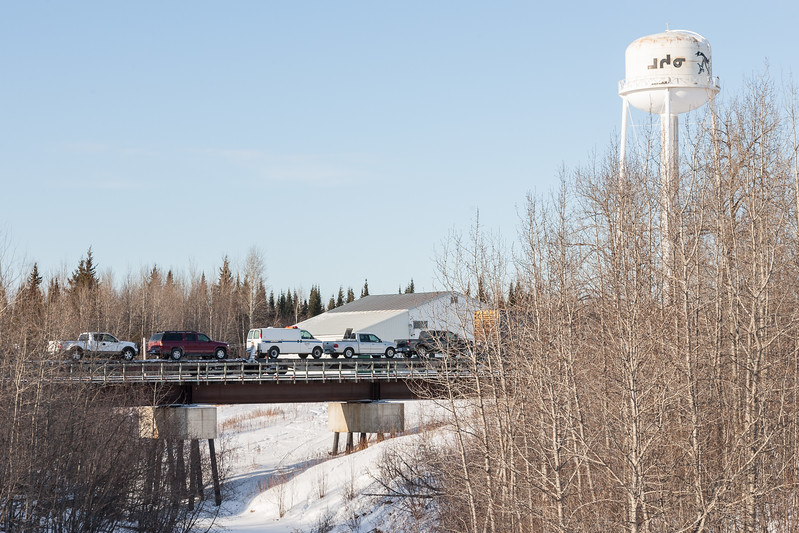 Vehicles on flatcars crosing Store Creek in Moosonee in the consist of the regular mixed train (Little Bear) 2007 February 16th. Vehicles include Ontario Provincial Police van.