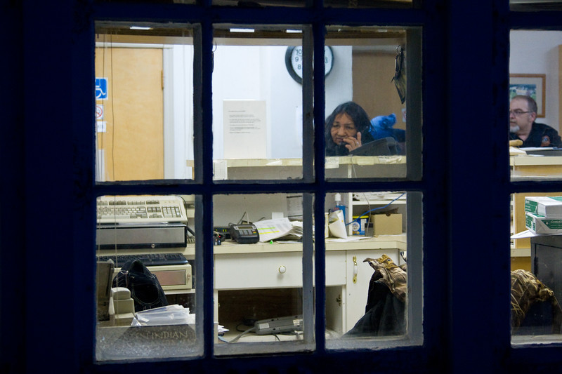 View through windows of Moosonee Train station. Customer Rachel Chakasim at left; agent Steve Baker at right. 2007 December 14th.