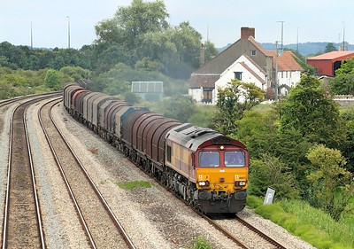 66183 powers away from Severn Tunnel Junction and passes Undy on the slow with 17.04 Round Oak to Margam empty steel carriers. 12/07/2011