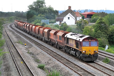 66009 heads a mixed rake of Ex RMC empty bogie hoppers past Undy as the 6Z42 Acton Yard to Cardiff Docks. 12/07/2011