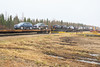 Locomotives pull out with newly arrived flatcars plus ones heading south.