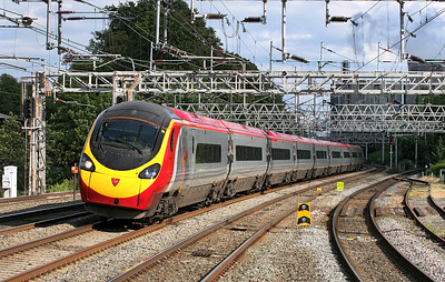 The 16.33 Euston to Preston Virgin Pendolino service formed of 390048 emerges from the shadows of the power station and passes Rugeley Trent Valley.