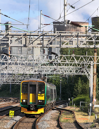 With Rugeley Power Station dominating the background 153365 & 170504 arrive at Rugeley Trent Valley off the Walsall route with a London Midland service from Birmingham New Street.