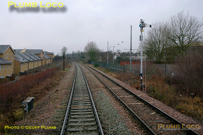 The old oil sidings can be seen on the right of the picture, long since severed from the main line. 960014 is about to pass Neasden Junction's up outer home signal for the opposite direction, for northbound trains, as it heads south. 11:16, Thursday 4th February 2010. Digital Image No. GMPI4392.