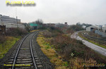 "960014 is now well round Neasden Curve and has climbed above the lines on the right to the aggregate depot, more or less built on the site of the old steam loco shed. Neasden Junction Signalbox can be seen above these lines and its semaphore home signals can be seen in the centre of the picture, with the signal for the curve in the ""off"" position. 11:14, Thursday 4th February 2010. Digital Image No. GMPI4382."