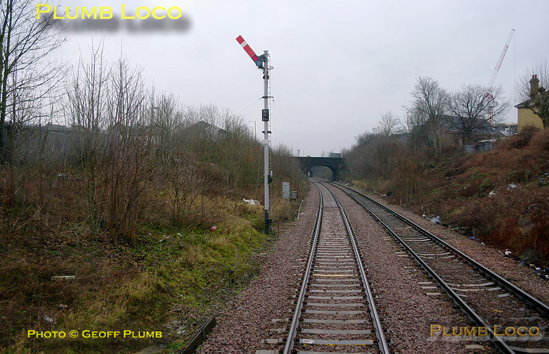"""960014 is now in the Harlesden area and has the all clear from signal NJ6, Neasden Junction's down advanced starter being in the """"off"""" position. The old station at Harlesden (Midland) was beyond the second of the two bridges visible, this station closed in 1902! 11:17, Thursday 4th February 2010. Digital Image No. GMPI4393."""