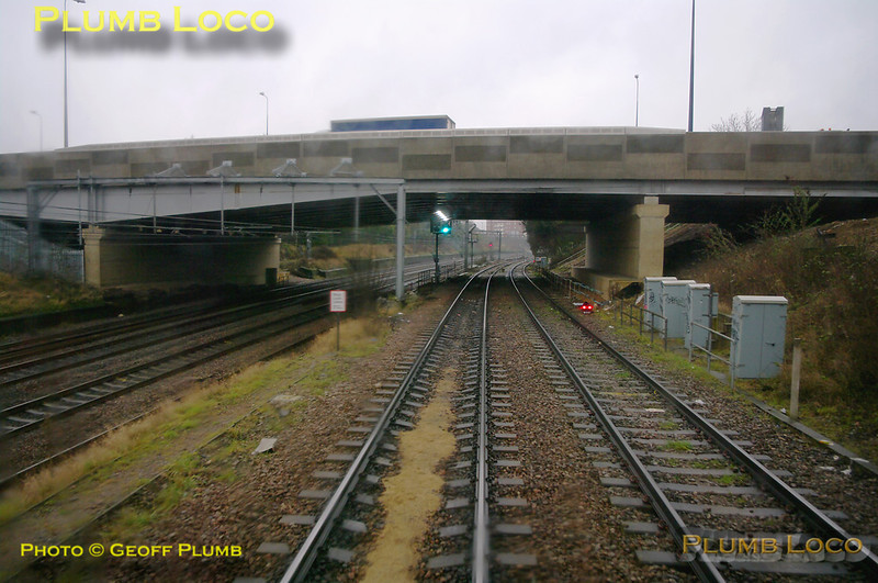 960014 is now dropping down Poplar Bank from Acton Wells Junction and is about to pass under the bridge carrying the A40 Western Avenue, recently rebuilt. Alongside on the left are the GWML tracks from Paddington and the green signal ahead has the left feather indicator to join the down relief line at Acton East Junction (aka Poplar Junction). 12:23, Thursday 4th February 2010. Digital Image No. GMPI4454.