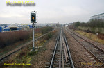 A pigeon has just taken flight from signal ACW34 as the bubblecar approaches. This is Acton Canal Wharf's down home signal and a three aspect colour light, showing a cautionary yellow aspect as we are to stop here and reverse onto the Acton Branch, seen below to the left, to gain the WCML. 11:19, Thursday 4th February 2010. Digital Image No. GMPI4400.
