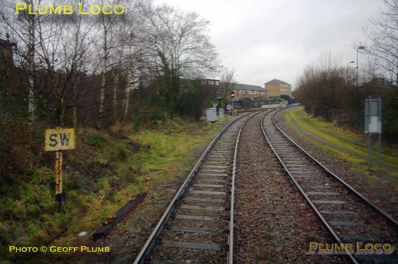 """Further round the east curve from West Ealing Junction and the lines from Hanwell Junction forming the west side of the triangle can be seen ahead at Drayton Green Junction, where the bubblecar has a yellow signal to proceed through Drayton Green station. On the left is an old GWR SW sign for """"Sound Whistle"""". 12:32, Thursday 4th February 2010. Digital Image No. GMPI4470."""