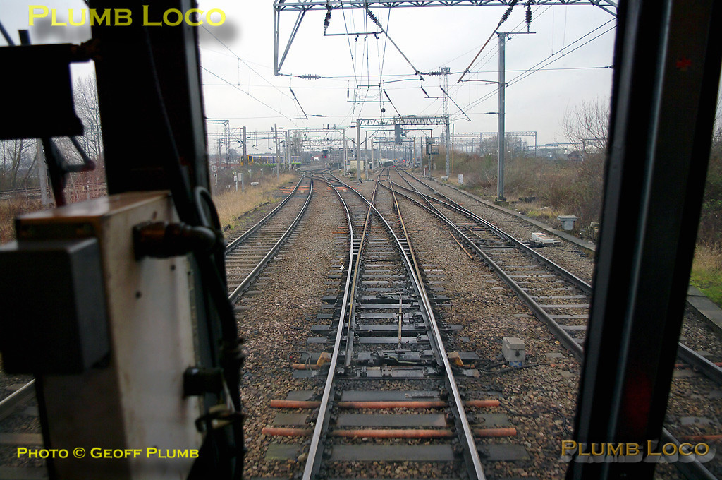 Having passed under the mainlines, the relief lines have now climbed back up to the same level as the bubblecar approaches Sudbury Junction, to join the relief lines direct from Euston, along which a northbound EMU can be seen to the left of centre. The lines cross the North Circular Road here on several bridges and the Royal Mail's Princess Royal Distribution Centre (PRDC) is just out of the picture to the right. This was the limit of the run in the bubblecar and reversal took place by the signals beyond the crossover to the left of centre. 11:30, Thursday 4th February 2010. Digital Image No. GMPI4428.