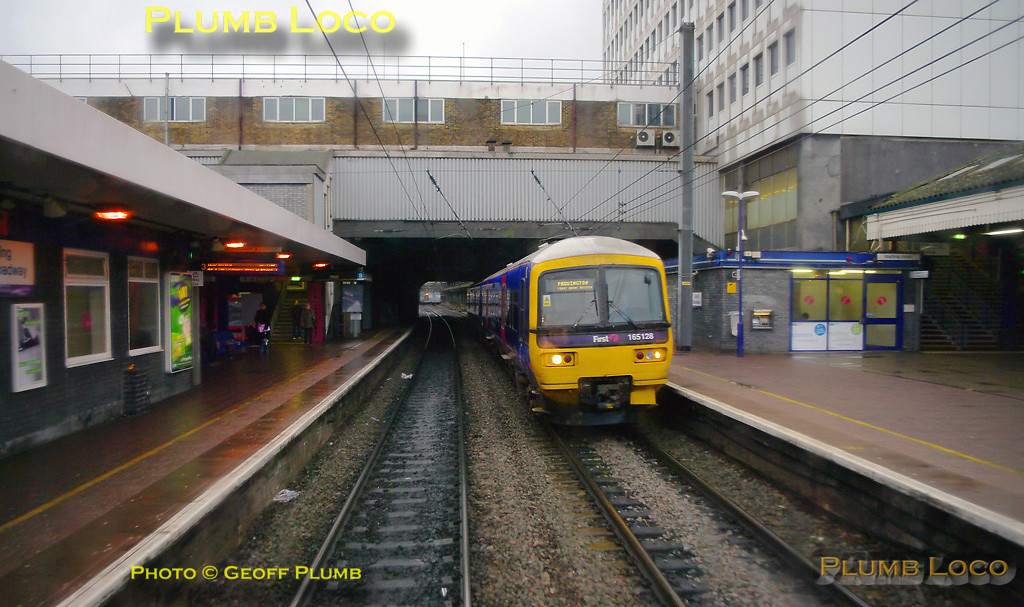 The bubblecar passes through Ealing Broadway station westbound, while FGW 165 128 passes in the opposite direction with an up stopping train. 12:28, Thursday 4th February 2010. Digital Image No. GMPI4465.