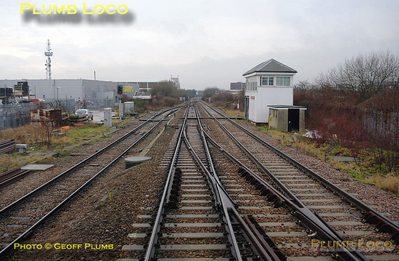 Acton Canal Wharf Junction has two crossovers, one in each direction, plus the junction with the Acton Branch, here seen trailing in from the left. This is protected by signal ACW21, showing a red aspect. The signalbox is another Midland Railway example, though much modified over the years. Near the box is another Midland relic in the form of the milepost, which is the 8½ milepost, measured from St. Pancras. 11:19, Thursday 4th February 2010. Digital Image No. GMPI4402.