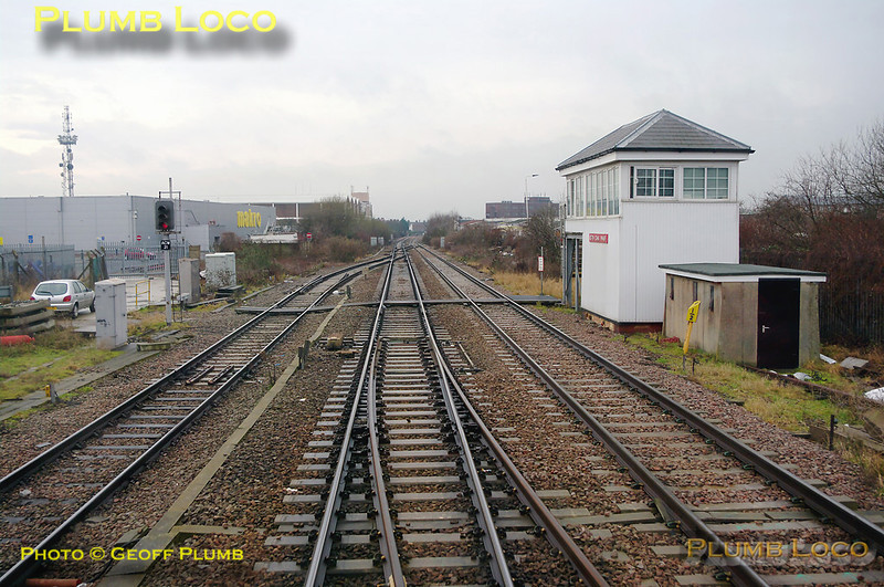 Acton Canal Wharf Junction has two crossovers, one in each direction, plus the junction with the Acton Branch, here seen trailing in from the left. This is protected by signal ACW21, showing a red aspect. The signalbox is another Midland Railway example, though much modified over the years. Near the box is another Midland relic in the form of the milepost, which is the 8½ milepost, measured from St. Pancras. 11:19, Thursday 4th February 2010. Digital Image No. GMPI4403.