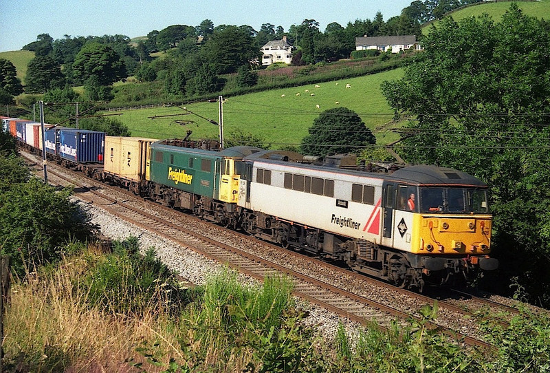 86628 Aldaniti and 86620 Phillip G Walton approach Oxenholme with a Freightliner from Coatbridge, 26/7/1999.