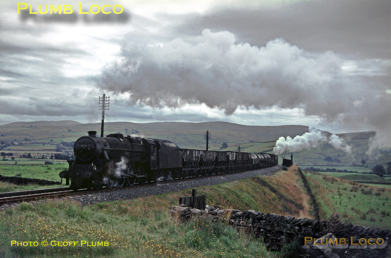 """""""Black 5"""" 4-6-0 No. 44948 is in charge of a mixed goods train as it heads north towards the Greenholme Road bridge on the climb of Shap. The driver had decided to forgo the services of the Oxenholme """"banker"""" for the climb of Grayrigg but decided that help would be a good idea on Shap! Tebay """"banker"""" No. 75039 helps out at the rear of the train. Saturday 19th August 1967. Slide No. 2988."""