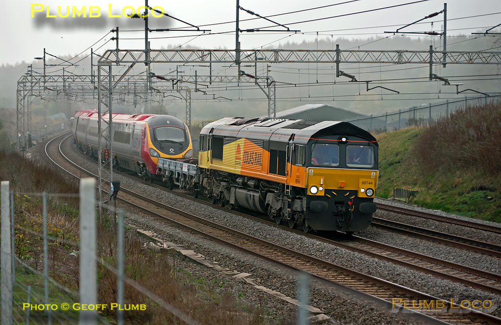 Colas Rail 66744 is in charge of 6X39, the 05:37 from Dollands Moor to Edge Hill, hauling newly delivered eleven car Pendolino 390 055 with a barrier wagon in between. It is passing Old Linslade on the down slow line at 09:07 on Wednesday 16th November 2011, another very dull morning. Digital Image No. GMPI10603.
