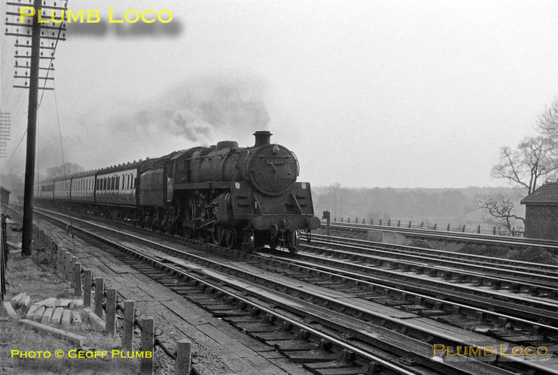 An unidentified (but possibly No. 73004) BR Standard 5MT 4-6-0  reaches the southern end of Bushey troughs on the down slow line with a stopping passenger train from Euston to Tring in March 1963. At this point the water troughs were inclined slightly upwards so that the water didn't run out of the ends!
