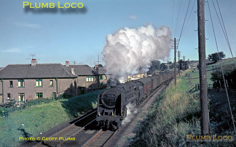 "From the Geoff Plumb Collection of original slides. BR Standard ""Britannia"" Class 4-6-2 No. 70038 ""Robin Hood"" is at the head of an up parcels and mail train, including a TPO behind the tender. On the southbound climb to Shap, it is passing through the village and approaching Shap station, possibly fairly early in the morning judging from the angle of the light, length of the shadows and the exhaust condensing quite well on Friday 27th August 1965. From information received, this could be 3K13, the 04:28 Carlisle to Crewe working, due into Preston around 08:30... Photo by Mike Burnett."