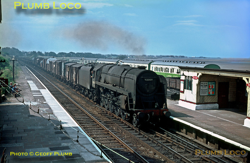 BR Standard 9F 2-10-0 No. 92009 heads north through Hest Bank station with a down fitted freight train. Note the Camping Coaches in the sidings and Morecambe pier in the distance. Wednesday 20th July 1966. Slide No. 2249.