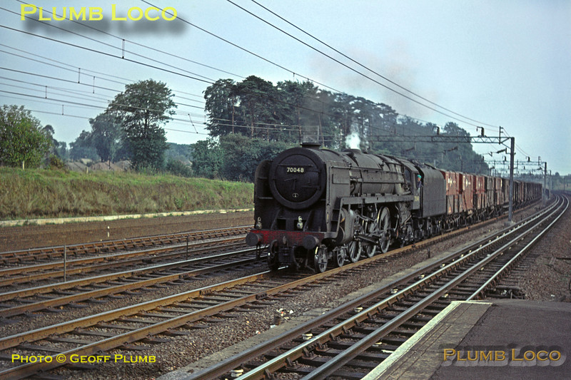 "BR Standard ""Britannia"" Class 4-6-2 No. 70048 ""The Territorial Army 1908-1958"" looks in typical run-down condition for the period, here in charge of a northbound fitted freight on the down fast line at Carpenders Park station, Saturday 5th September 1964. Slide No. 1053."