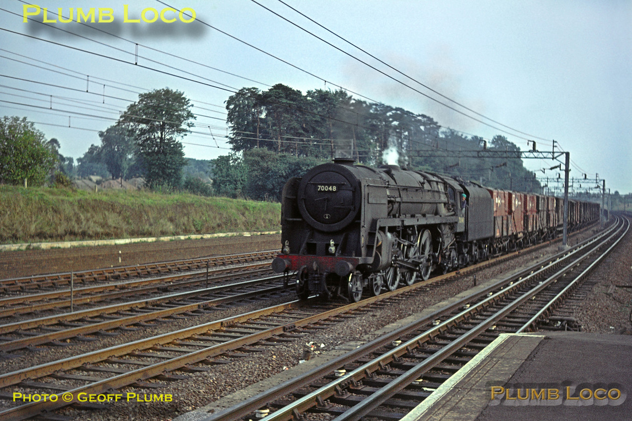 """BR Standard """"Britannia"""" Class 4-6-2 No. 70048 """"The Territorial Army 1908-1958"""" looks in typical run-down condition for the period, here in charge of a northbound fitted freight on the down fast line at Carpenders Park station, Saturday 5th September 1964. Slide No. 1053."""