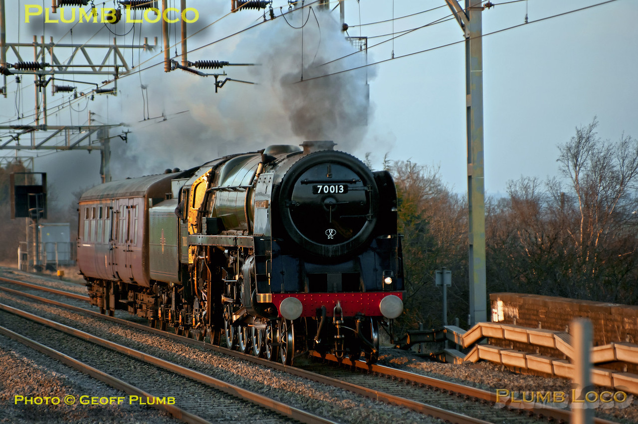 """BR Standard """"Britannia"""" 4-6-2 No. 70013 """"Oliver Cromwell"""" with its support coach in tow approaches Cheddington station with 5Z57, Carnforth to Southall move prior to its booked working for the following Saturday. It just catches the last rays of the setting sun at 17:07 on Thursday 1st March 2012. Digital Image No. GMPI11190."""