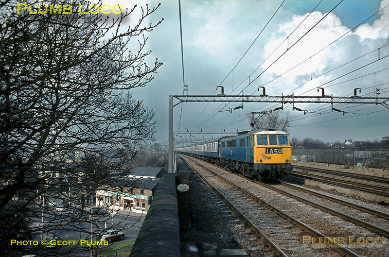 An unidentified BR 25Kv Bo-Bo electric of Class AL6 (later Class 86) heads south on the up fast line crossing the bridge over the road as it approaches Bushey & Oxhey station with an express to Euston, 1A50, consisting of a mix of Mark I and Mark II stock in blue & grey livery. April 1970. Slide No. 4757.