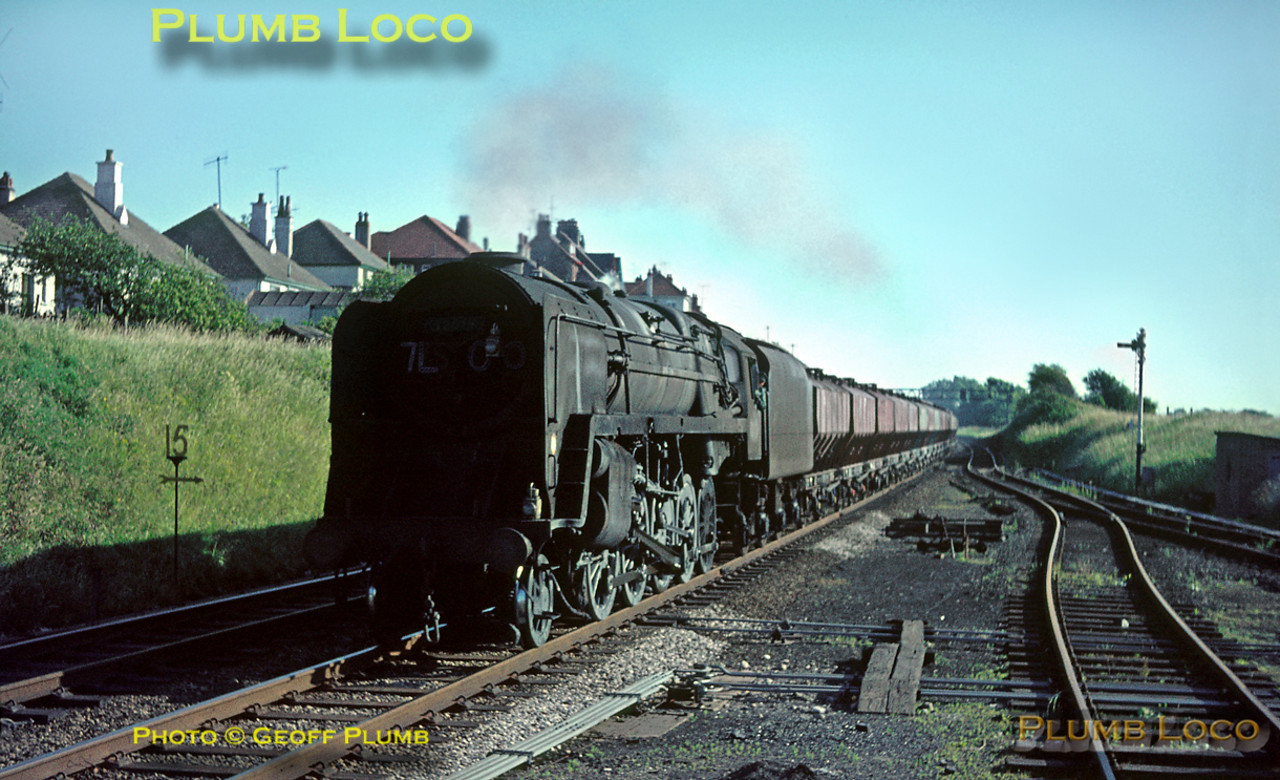 BR Standard 9F 2-10-0 No. 92015 is about to pass through Hest Bank station with a down goods train of mineral hopper wagons on Thursday 21st July 1966. Slide No. 2300.
