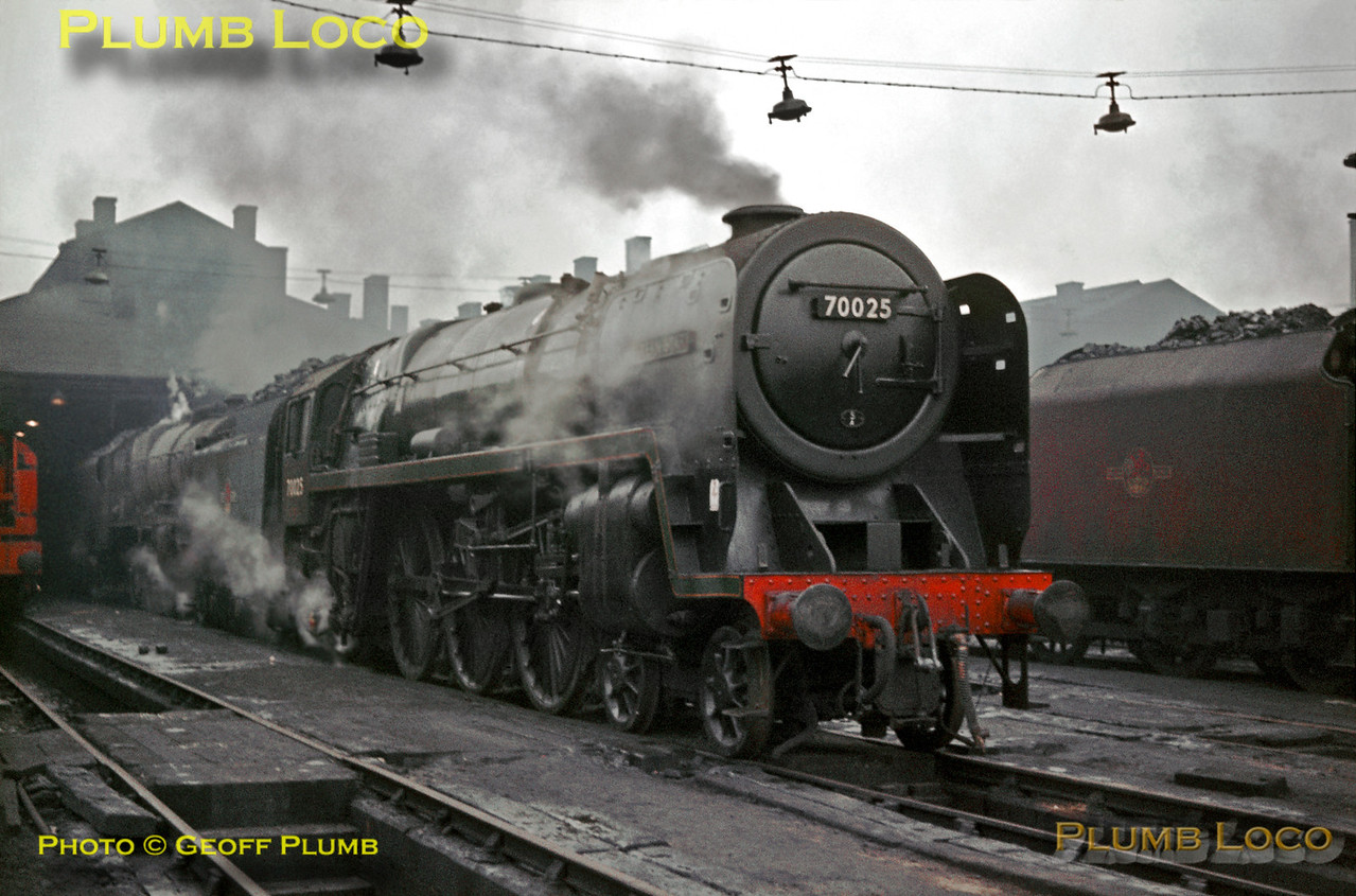 """Sunday 5th January 1964 was a very dull day at Willesden MPD, but many engines were stabled there. BR Standard """"Britannia"""" 4-6-2 No. 70025 """"Western Star"""", allocated to Crewe North MPD (5A), was amongst them, along with an unidentified """"Royal Scot"""" 4-6-0 behind it and the almost maroon liveried tender of 46240 """"City of Coventry"""" is alongside. The steam breakdown crane just edges into the picture on the extreme left. Slide No. 484."""
