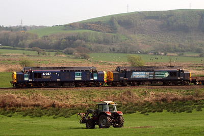 A farmer goes about his business as 37087 and 37667 head 6K73 past Linethwaite. 19/04/11.