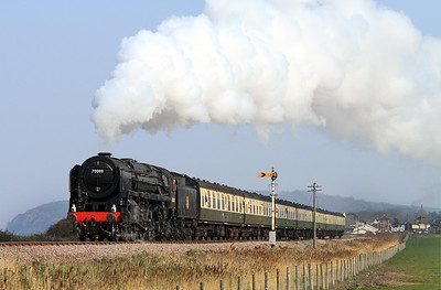 70000 'Britannia' in unlined black and without nameplates heads the 13.00 Bishops Lydeard to Minehead away from Blue Anchor.