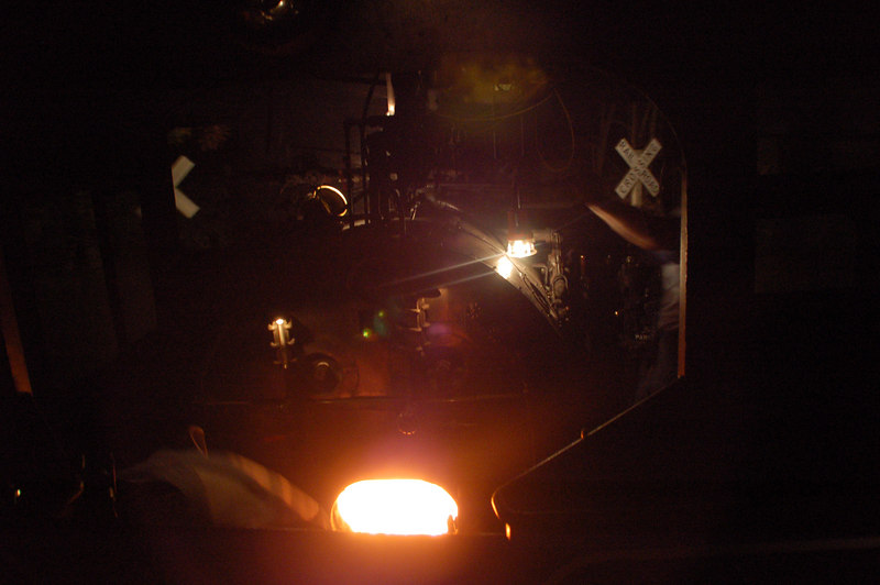 Once in a while, you get come up with a photo that turns out totally different from what it looked like through the lens.   This shot was taken from the coach behind the engine.   The crossbucks at a crossing are visible through both windows of the engine.   The engineer is leaning out of the cab and you can see his left arm/hand on the throttle (below the crossbucks on the right).  A brakeman's lantern is hanging off of the throttle.   The fireman is shovelling coal into the fire box (you can see him bent over to the left of door to the firebox), and the open door gives off an erie glow.