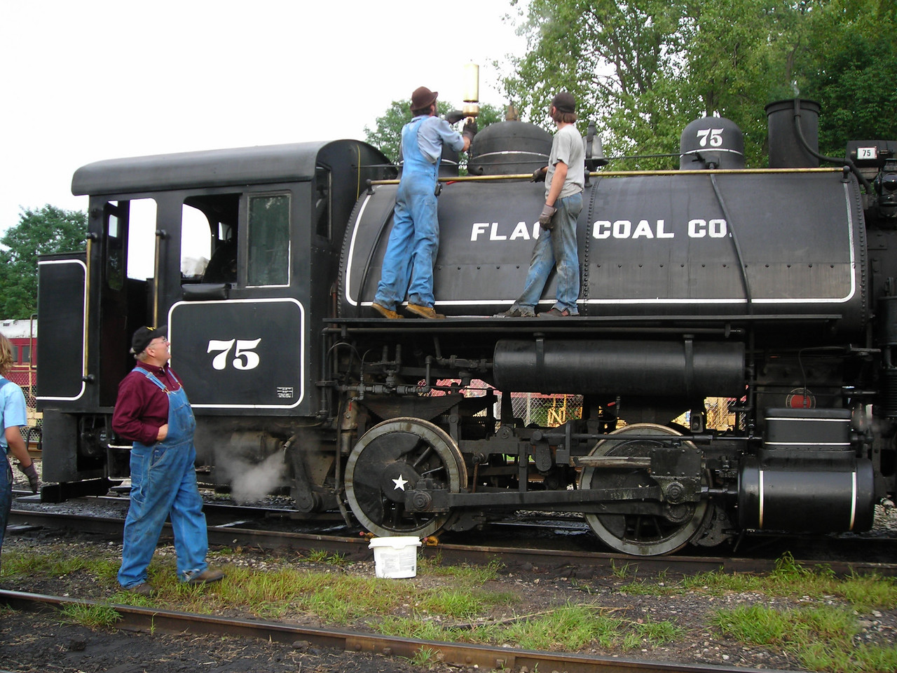 "Many of the crew of the WVRR have at least one steam whistle that they have collected.   While operating as the engineer, the honor is given for them to put their own whistle on the engine.   In this photo, an engineer is installing a large whistle on FCC 75.   Due to its size, the whistle could not be used while in motion (low hanging tree branches).   However, that did not stop the crew from doing a ""stationary test""."