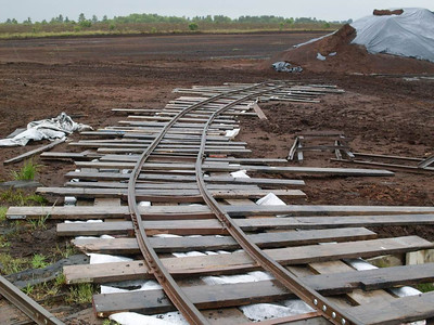 "The rather temporary looking curve leading fro the ""main line"" to the large peat stack which was being loaded onto trains on this day, a derailment having meant plans were changed at short notice. The use of sleepers of various lengths and various planks is interesting."