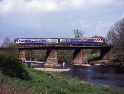 Children paddle in the river Kent in Kendal as a class 150 DMU passes overhead on Mayday bank holiday 1/5/00.