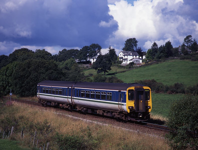 Under a threatening sky 156427 forms a Windermere-Oxenholme service approaching Bowston 20/8/00