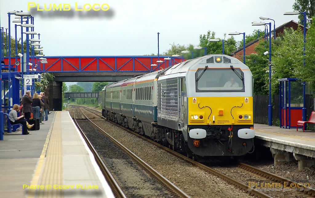 """67015 had been bulled-up including silver buffers for its naming ceremony the day before - it was given the name """"David J Lloyd"""" to commemorate a local railway activist at Gobowen station on Friday 16th May 2008. On Saturday 17th May it is partnering fellow W&S liveried 67013 topping & tailing 1J86, the 12:17 train from Marylebone to Wrexham, having worked up from Wrexham as 1P01, the 05:51 departure from Wrexham, comprising the four coach set. It is passing through Haddenham & Thame Parkway station on time at 12:58. This was the first time I had seen a train with W&S liveried locos on each end since the """"real"""" service began and also the first time the loco was facing the """"right"""" way, with the darker silver end at the outer end of the train - though 67013 on the rear was the """"wrong"""" way round! Digital Image No. IMGP4948."""