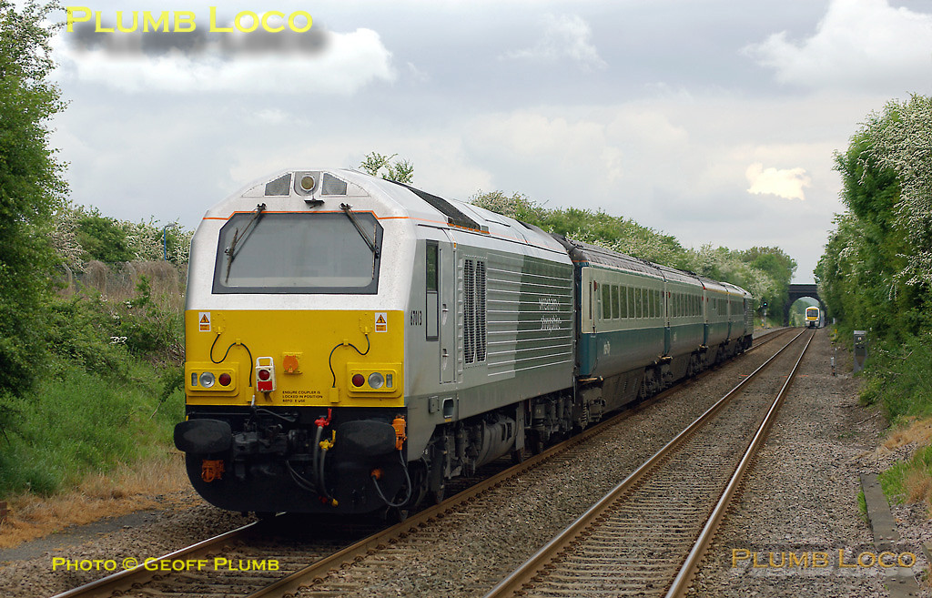 """67015 had been bulled-up including silver buffers for its naming ceremony the day before - it was given the name """"David J Lloyd"""" to commemorate a local railway activist at Gobowen station on Friday 16th May 2008. On Saturday 17th May it is partnering fellow W&S liveried 67013 topping & tailing 1J86, the 12:17 train from Marylebone to Wrexham, having worked up from Wrexham as 1P01, the 05:51 departure from Wrexham, comprising the four coach set. It is passing through Haddenham & Thame Parkway station on time at 12:58. This was the first time I had seen a train with W&S liveried locos on each end since the """"real"""" service began and also the first time the loco was facing the """"right"""" way, with the darker silver end at the outer end of the train - though 67013 on the rear was the """"wrong"""" way round! Digital Image No. IMGP4951."""