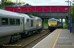 """In a nice coincidence of timing during the first day of extra Chiltern LHCS services, trains pass at Haddenham & Thame Parkway station. On the left is 67013 """"Dyfrbont Pontcysyllte"""" which has stopped at the station with 1H53, the 15:55 from Birmingham Moor Street to Marylebone. Approaching at high speed is 1R47, the 16:30 from Marylebone to Birmingham Moor Street, DVT 82305 leading the train with 67012 """"A Shropshire Lad"""" on the rear. 17:13, Monday 23rd May 2011. Digital Image No. GMPI9217."""