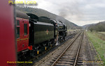 """2-10-0 92214 was at the head of the 12:00 train from Pickering to Whitby, but as the loco is not passed to run on Network Rail it was exchanged with """"Black 5"""" 45428 at Levisham, so that 45428 could work through to Whitby. The 9F has now taken over the southbound train and waits to depart, seen from the rear of the northbound train. 12:36, Monday 11th April 2011. Digital Image No. GMPI8586."""