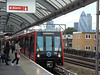 New DLR unit 122 at Shadwell, with the City's skyline in the background. Fri 20th August 2010.