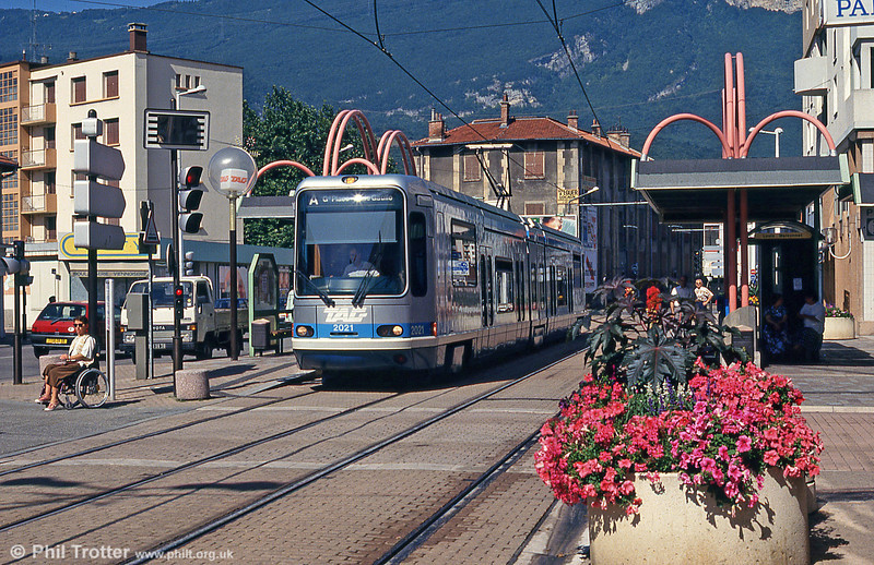 A wheelchair user, travelling independently, moves away from the tram stop at Charles Michels as Grenoble car 2021 pulls away on 28th July 1993.