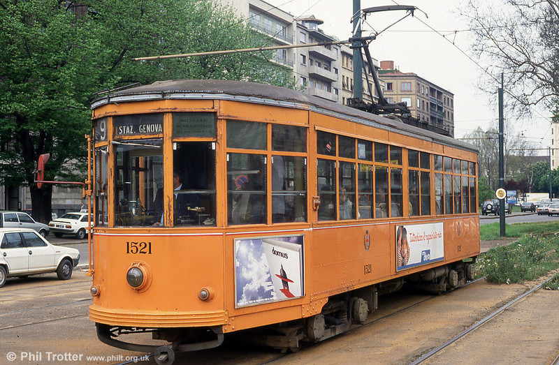 Peter Witt car 1597 at Piazza della Repubblica on 21st April 1992. This type of car is named after Cleveland street railway commissioner Peter Witt, who designed it for Ohio around 1915. The concept was to speed loading by putting the conductor in the middle of the car, letting crowds board through the front door and paying as they passed the conductor.<br /> Milan has the longest-serving Peter Witts in the world, building some 500 from 1928. The first Peter Witts in Milan were painted an attractive yellow and white; in the 1970s, the Milan tram fleet was repainted a solid orange. The Peter Witt trams no longer use conductors.