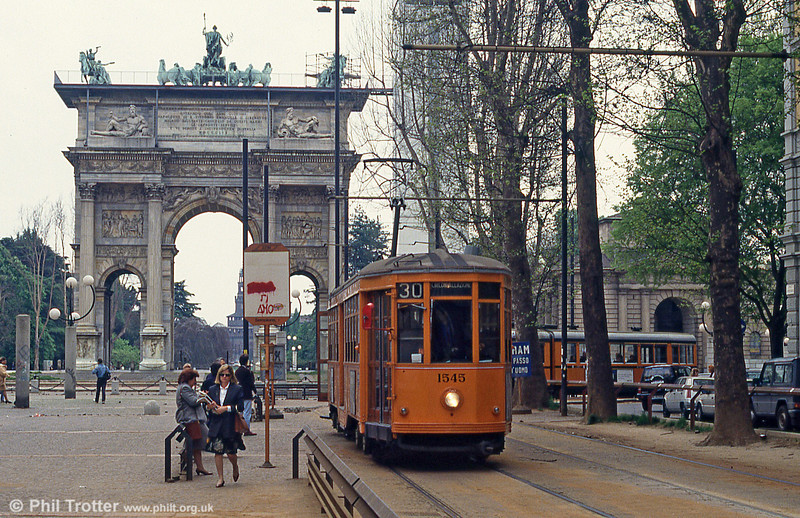 Car 1545 at Piazza Sempione on 21st April 1992. Porta Sempione (Simplon Gate) is a former city gate to Milan. The name 'Porta Sempione' is used both to refer to the gate proper and to the surrounding district. The gate is marked by a landmark triumphal arch called Arco della Pace (Arch of Peace), dating back to the 19th century but its origins can be traced back to a gate of the Roman walls of Milan.