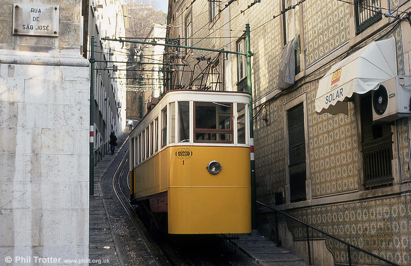 Inaugurated in 1884, the Lavra funicular was the first transportation of this typed to defy the gravity laws and to provide one of Lisbon's most steep areas, linking the Largo da Anunciada and the Travessa do Forno do Torel. It runs from the eastern side of the Avenida da Liberdade, near Restauradores Square, at a 25% gradient for 180 metres.<br /> The Lavra funicular has the capacity for 22 people seating and 20 standing, and the journey takes about 2 minutes. Car 1 is seen on 25th November 1993.