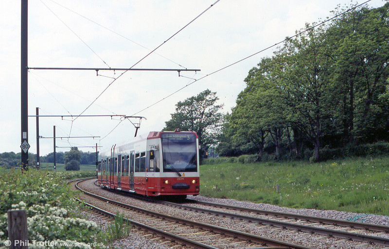 A flavour of a rural tramway - but this is London! Croydon 2534 near Gravel Hill on 15th May 2004. The cars have a top speed of 50mph.